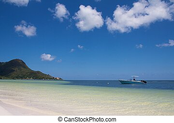Lonely boat at the white shores of Praslin island, Seychelles with a mountain in the background