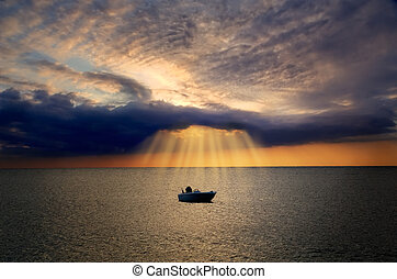 Lonely boat floating in sea is lit by divine light from dark cloud during sunset