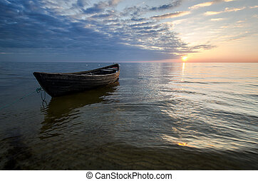 Lonely boat on the sea at sunset.