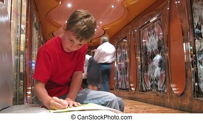 Lonely boy draws picture in corridor full of tourists, time...