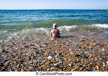 Lonely boy sitting in the sea