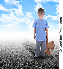 A young boy is holding a teddy bear and standing on an empty road with clouds in the sky. His shadow is in the horizon.