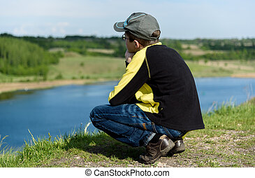 lonely boy teenager sits on a hill above lake