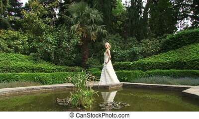 Lonely bride - Bride walking alone on a green park with a...