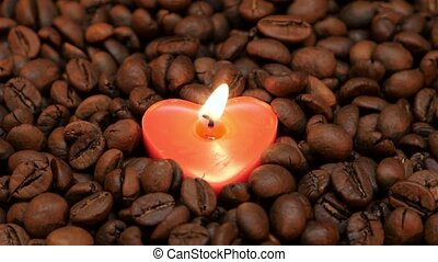 Lonely burning candle in the shape of heart. Closeup