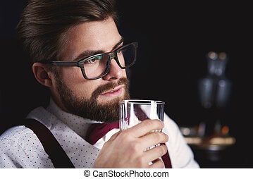 Lonely business person tasting whiskey