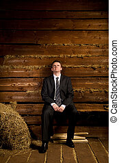 lonely businessman sitting on bench near haystack in wooden log hut