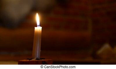 Lonely candle in a dark room.
