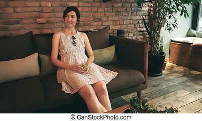 Lonely Caucasian woman in dress waiting her date in a cafe...