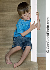 Lonely child - Concept of Child Abuse: Lonely boy sits on ...