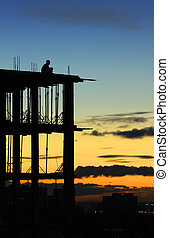 Lonely construction worker sitting at the edge of unfinished...