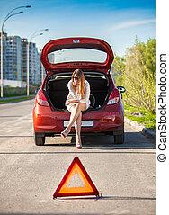 depressed woman sitting on trunk of broken car