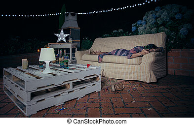 Lonely drunk woman sleeping over a sofa after party