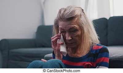 Lonely elderly woman wiping tears with a tissue. Loneliness at old age. High quality 4k footage