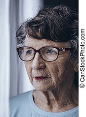 Lonely elderly woman with glasses
