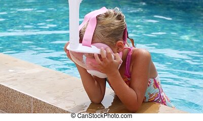 Lonely first-grader girl in the pool. Pandemic, lockdown.
