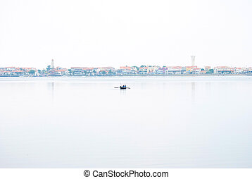 Lonely fishing boat on transparent water