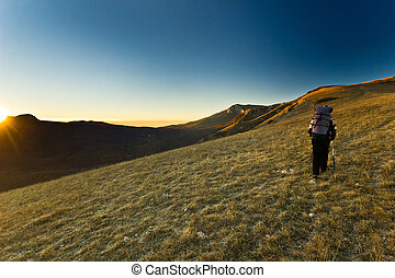 lonely girl hiking in the mountains at sunrise