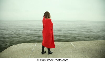 Lonely girl in red blanket looking