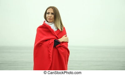 Lonely girl in red blanket on pier