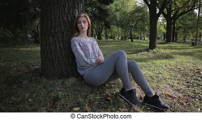 Lonely girl in sports form is bored sitting under a tree