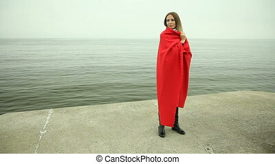 Lonely girl pensive in red blanket