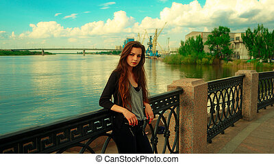 LOnely girl posing leaning back against embankment fence and background with river and wharf cranes