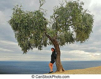 Lonely girl stands under a tree on the seashore in autumn