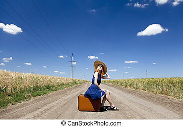 Lonely girl with suitcase at country road.