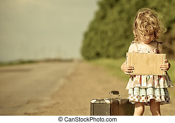 Lonely girl with suitcase standing about road and holding...