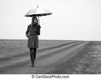 Lonely girl with umbrella at country road.