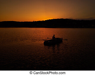 Lonely guy sitting in a boat at sunset.