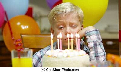 Lonely holiday - Sad little boy celebrating his birthday...