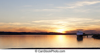 Lonely house and lake - Sunset landscape.Lonely house and...