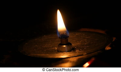Lonely iron funeral candle on sand in catholic temple. Candlelight in dark