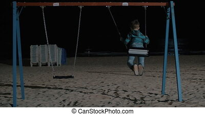 Lonely kid swinging on the beach at night