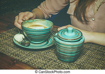 Lonely lady drinking coffee in the morning, side view of female hands holding stripped cup of hot beverage on wooden desk.
