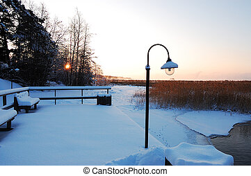 Lonely lantern on the snow covered pier at sunrise