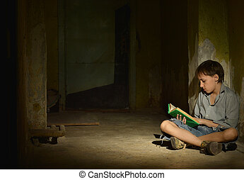 Lonely little boy reading book