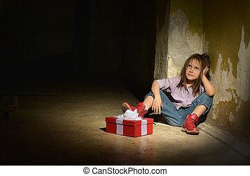 Lonely little girl in a dark cellar