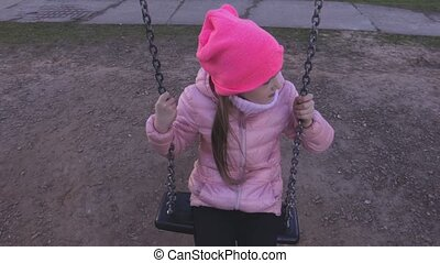 Lonely little girl on the swing