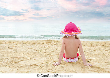 Lonely little girl watching the waves at the beach