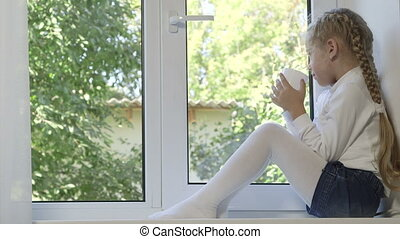 Lonely little girl with cup of drink looking out the window