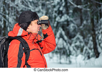 lonely lost tourist man in winter forest with binoculars looking to the right