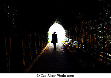 Lonely man is walking through dark tunnel to the light