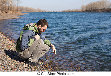 Lonely man on a river bank