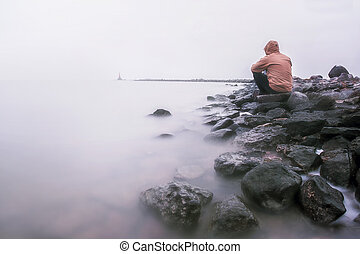 lonely man on the shore of a foggy sea