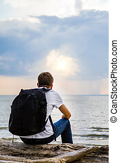 Lonely Man outdoor - Lonely Young Man with Backpack sit on...