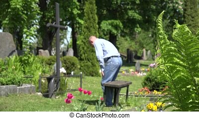 lonely man sit on bench to marble cross in country cemetery....