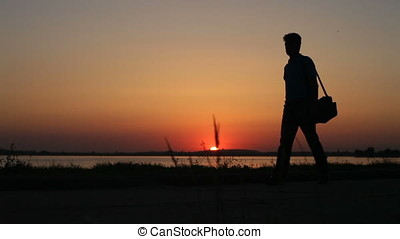 Lonely Man With Bag Walking On Lake Shore Sunset Backlit Silhouette